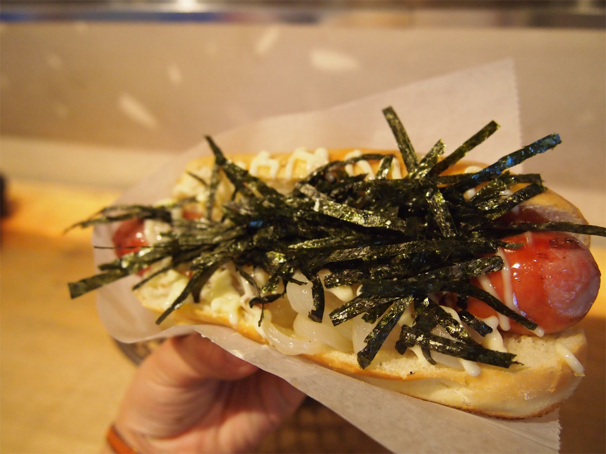 JAPADOG's recommendation, KUROBUTA TERIMAYO that has its original sausage made of  a rare breed of pigs called Berkshire with Teriyaki sauce, onion and chopped nori. Photo courtesy: Mizuki Ogi